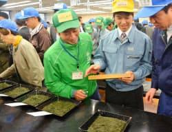 「新茶初取引」で交渉する関係者(24日午前、静岡市の静岡茶市場)=共同
