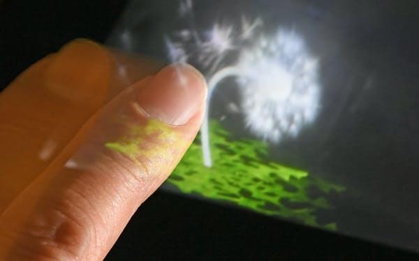 空中で指を振ると、立体的に映し出されたタンポポが揺れて綿毛が舞うように見える(パリティ・イノベーションズの研究所)