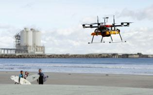 10キロを超える距離を完全自律制御で試験飛行し、海岸線で待つサーファーに飲み物を届ける小型無人機「ドローン」(12日午前、福島県南相馬市の北泉海水浴場)