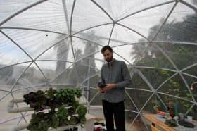 flux IoTのEddy(男性が持っている装置)は植物の状態を感知し、農業従事者に伝える機能を備える(火星での植物栽培を実験するハウスの中)