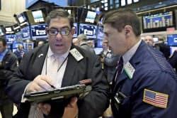 5日、ニューヨーク証券取引所で働くトレーダーら=AP