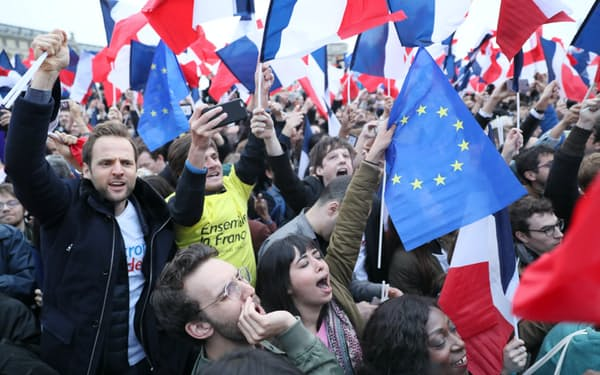 マクロン候補が勝利を確実にしたとするテレビの報に喜ぶ人たち(7日、パリ)=浅原敬一郎撮影