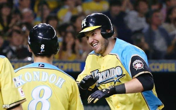 3回、4打数連続本塁打のプロ野球記録に並ぶ2ランを放ち、近藤(左)に迎えられる日本ハムのレアード(13日、東京ドーム)=共同