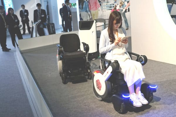 利用者はスマートフォンから電動車いすや「追従走行カートロボット」に指示を出す(都内で2月に開かれたデモンストレーションの様子)