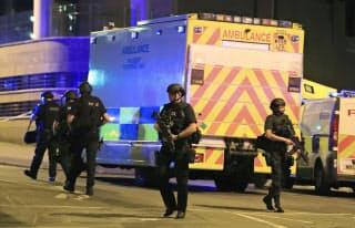 大きな爆発音がしたコンサート会場周辺を警戒する武装警察官(22日、英中部マンチェスター)=AP