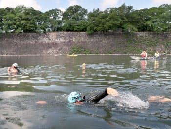 大阪城の堀で泳ぐ大阪府トライアスロン協会の理事ら(26日午前、大阪市中央区)