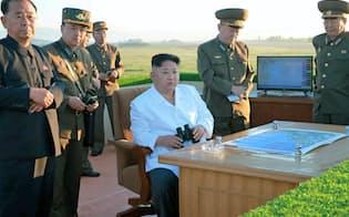 北朝鮮の労働新聞が28日掲載した、国防科学院による新型の対空迎撃ミサイルシステムの試験発射を視察する金正恩朝鮮労働党委員長(右から3人目)の写真(共同)