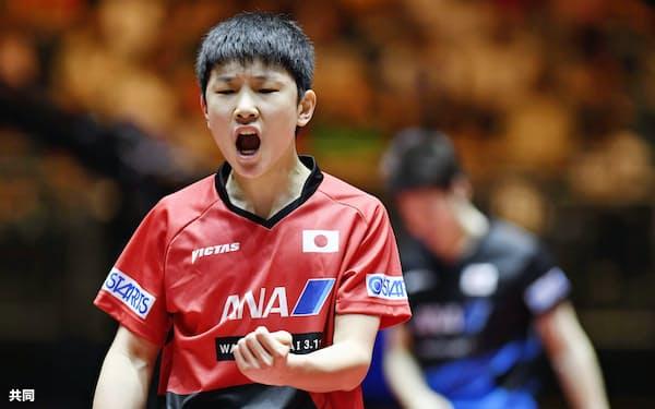 男子シングルス2回戦で水谷隼(奥)からポイントを奪い、ガッツポーズする張本智和=共同