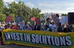 1日、ホワイトハウスの外に集まりトランプ米大統領のパリ協定離脱表明に抗議する人々=AP