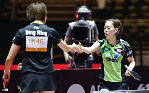 女子シングルス準々決勝で敗退し、中国の丁寧(左)と握手する石川佳純(2日、デュッセルドルフ)=共同
