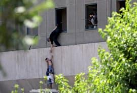 襲撃事件があった国会議事堂の窓から脱出する少年(7日、テヘラン)=ロイター