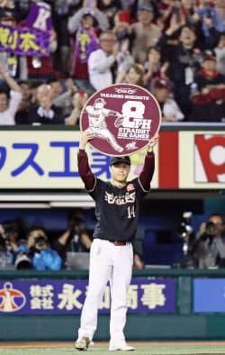 自身の持つプロ野球記録を更新する8試合連続2桁奪三振を達成し、記念のボードを掲げる楽天・則本(8日、Koboパーク宮城)=共同