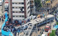 電車が脱線転覆し、線路脇のマンションに激突したJR福知山線の事故現場(2005年4月25日、兵庫県尼崎市)