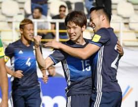 日本―イラクの前半、先制ゴールを決め、吉田(右)と抱き合って喜ぶ大迫。左奥は本田(13日、テヘラン)=共同