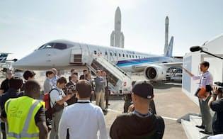 「パリ国際航空ショー」を前に、MRJの試験機の前で打ち合わせをする三菱航空機の担当者ら(18日、パリ近郊のルブルジェ空港)=共同