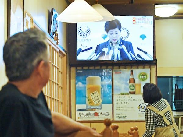 市場関係者が利用する飲食店のテレビに映し出される小池都知事の記者会見(20日午後、東京・築地の場外市場)