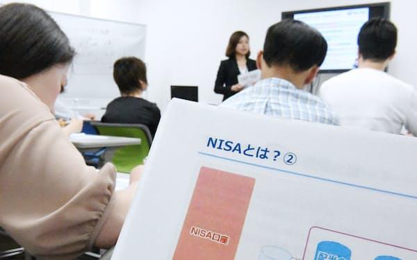 資産運用セミナーでNISAの説明を聞く人たち(東京都新宿区)