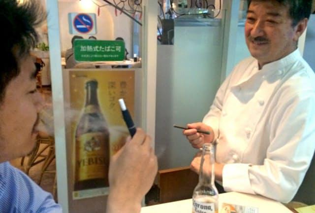 メキシコ料理店「TIOTIA」は禁煙の店内に「加熱式たばこ可」と表示、松田和典オーナー(右)がお客さんに薦めることもある(群馬県高崎市)