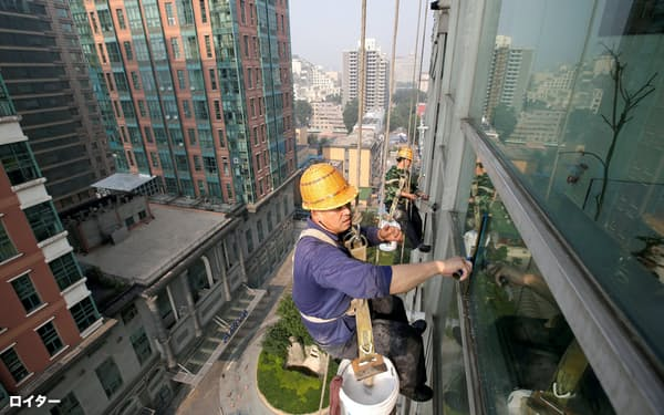 FILE PHOTO: Workers clean the windows of an apartment block in Beijing, China, June 27, 2017. REUTERS/Jason Lee/File Photo