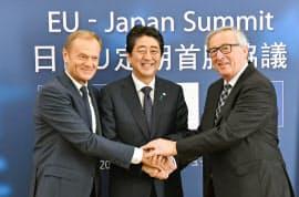 EUのトゥスク大統領(左)、ユンケル欧州委員長(右)と握手を交わす安倍首相(6日、ブリュッセル)=代表撮影、共同