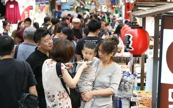 黒門市場で食べ歩きをする中国人観光客(大阪市中央区)