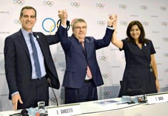 IOC臨時総会後の記者会見を終え、手を取り合う(左から)ロサンゼルスのガーセッティ市長、バッハ会長、パリのイダルゴ市長=共同
