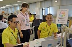万博誘致ロゴが入ったポロシャツを着て業務にあたる職員(20日、大阪市役所)