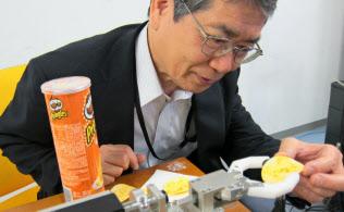 ポテトチップスを割らずにつかむ力加減を、ロボットアームに記憶させる大西教授(川崎市の慶応義塾大新川崎タウンキャンパス)