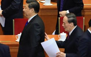習近平国家主席(左)に話しかける王岐山政治局常務委員(2016年3月、北京の人民大会堂)