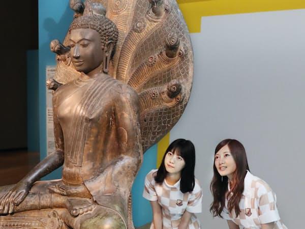 「ナーガ上の仏陀坐像」に見入る乃木坂46の白石麻衣さん(右)と西野七瀬さん