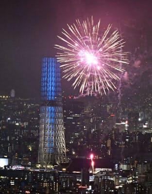 あいにくの雨の中、打ち上げられた隅田川の花火(29日夜)=共同