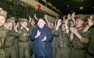 北朝鮮の労働新聞が29日掲載した、「火星14」発射に立ち会い、笑顔で拍手する金正恩朝鮮労働党委員長(中央)の写真=共同