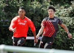 陸上世界選手権の公開練習でバトン練習をする桐生祥秀(右)とサニブラウン・ハキーム(31日、ロンドン)=共同