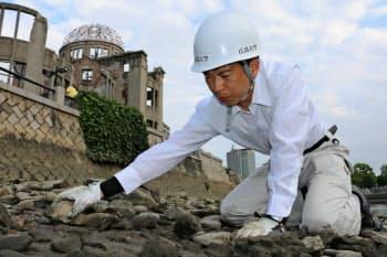 被爆した遺物を探す広島大の嘉陽さん(7月26日、広島市中区の元安川)