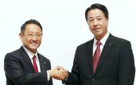 資本提携発表の記者会見で握手するトヨタ自動車の豊田社長(左)とマツダの小飼社長(4日午後、東京都中央区)