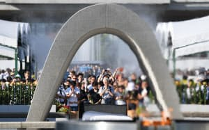 原爆慰霊碑に向かい祈りをささげる人たち(6日午前、広島市の平和記念公園)