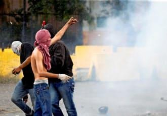 6日、攻撃があった軍基地の付近でベネズエラ政府に抗議する市民ら(北中部バレンシア)=ロイター