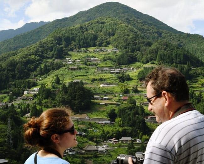 山あいに民家が点在する落合集落を見学。アルベール・ブルメールさん(49)は「日本は人が多くて窮屈というイメージだったが、これほど緑豊かな場所があったとは」と笑顔で話した