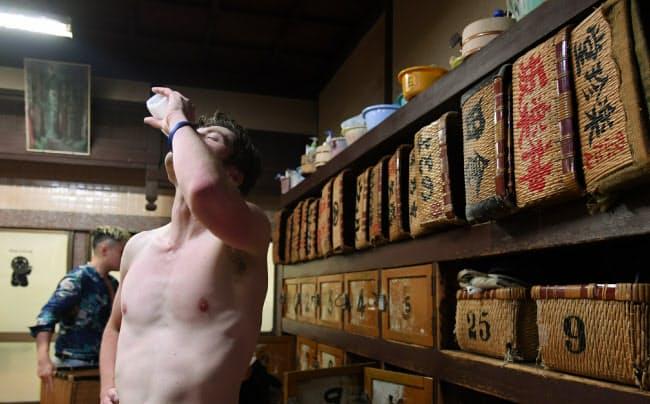 湯上がりに牛乳を飲むウオーカーさん。「錦湯」の長谷川泰雄さんは「湯に入ってリラックスした顔はみな同じ。国や民族の違いはありませんね」と話す