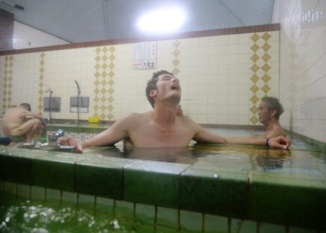 京都の老舗銭湯「錦湯」でくつろぐ米国人のジュリアン・チャイルズ・ウオーカーさん(26)。「人前で裸になる経験は初めて」と言いながらも、ゆったりと湯に漬かっていた(京都市中京区)