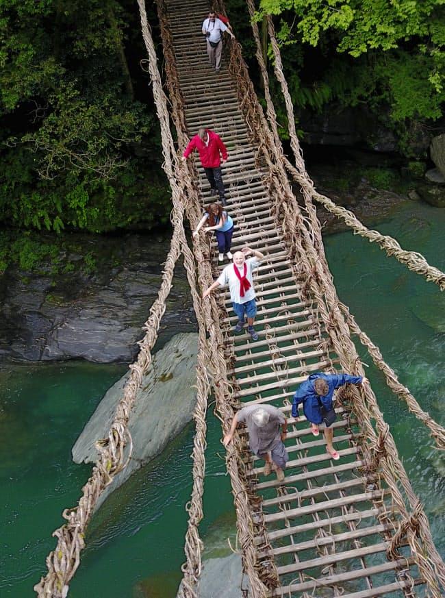 一歩ごとにぐらりと揺れる高さ14メートルの「祖谷(いや)のかずら橋」。フランス人観光客がこわごわと渡り、対岸に着くとほっとした表情を見せた=ドローンで撮影