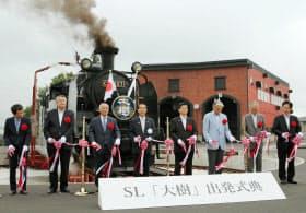 東武鉄道の蒸気機関車復活運行でテープカットをする関係者(10日午前、栃木県日光市)=共同