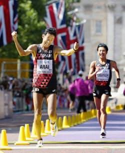 陸上の世界選手権男子50キロ競歩で銀メダルを獲得し、ガッツポーズの荒井広宙(左)と銅メダルの小林快(13日、ロンドン)=共同