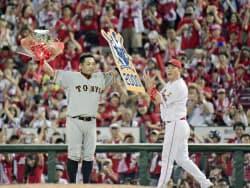 プロ野球広島戦で通算2千安打を達成し、花束を掲げる巨人の阿部慎之助内野手。右は祝福する広島の新井貴浩内野手(13日、広島市のマツダスタジアム)=共同