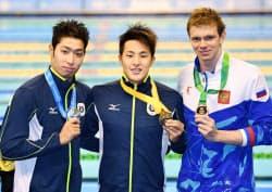 競泳男子400メートル個人メドレーで金メダルを獲得した瀬戸大也(中央)と銀メダルの萩野公介(左、26日、台北近郊)=共同