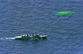 海上自衛隊のヘリが墜落したとみられる現場周辺を捜索する海自の護衛艦。右上は自衛隊が海上に漂わせている目印=27日午前11時1分、青森県竜飛崎の西南西約90キロ沖(共同通信社機から)