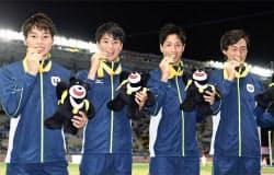 陸上男子400メートルリレーで優勝し、金メダルをかむ(左から)田中、多田、北川翔、山下(28日、台北)=共同