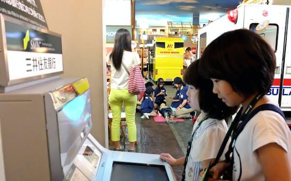 キッザニア東京のATMでキッゾの入出金や残高確認を行う子どもたち(東京都江東区)