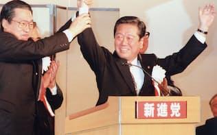 新進党党首(当時)に再選され、鹿野氏(左)とともに壇上に上がる小沢氏(1997年12月)
