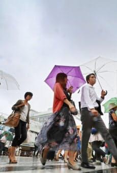 雨の中、傘を差して歩く人たち(31日、東京・新宿)